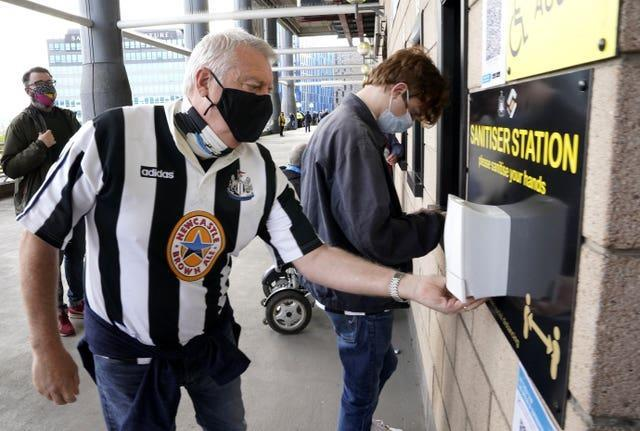 Face mask-wearing Newcastle fans use a hand sanitising station ahead of the Premier League match against Sheffield United at St James' Park. Despite the season ending on the high of having supporters back in stadia, the experience of attending matches is noticeably different to pre-pandemic conditions. Football fans will have to adapt to a 'new normal' at grounds, with the wait for the return of capacity crowds set to continue for the foreseeable future (Owen Humphreys/PA)