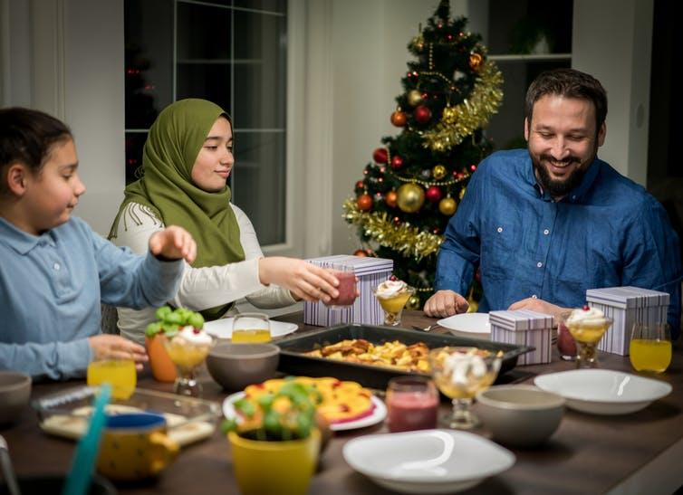 Interfaith family sat having dinner with Christmas tree in the background