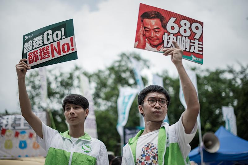 Pro-democracy activists display placards before a pro-democracy rally in Hong Kong on July 1, 2014 as frustration grows over the influence of Beijing on the city (AFP Photo/Philippe Lopez)