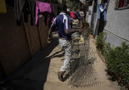A Haitian migrant carries the coils of a mattress to sell near his house in the Bosque Hermoso camp settled by migrants in Lampa, Chile, Friday, Oct. 1, 2021. Many of the wave of Haitians migrants who reached the U.S. border city of Del Rio, Texas in September began their long journey north from Chile, frustrated by the long waits, bureaucratic barriers and rejected applications here. (AP Photo/Esteban Felix)
