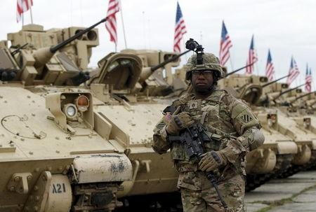 A member of the U.S. mechanized infantry company form 1st Brigade, 3rd Infantry Division walks past Bradley infantry fighting vehicles ahead an official opening ceremony of the joint U.S.-Georgian exercise Noble Partner 2015 at the Vaziani training area outside Tbilisi, Georgia, May 11, 2015. REUTERS/David Mdzinarishvili
