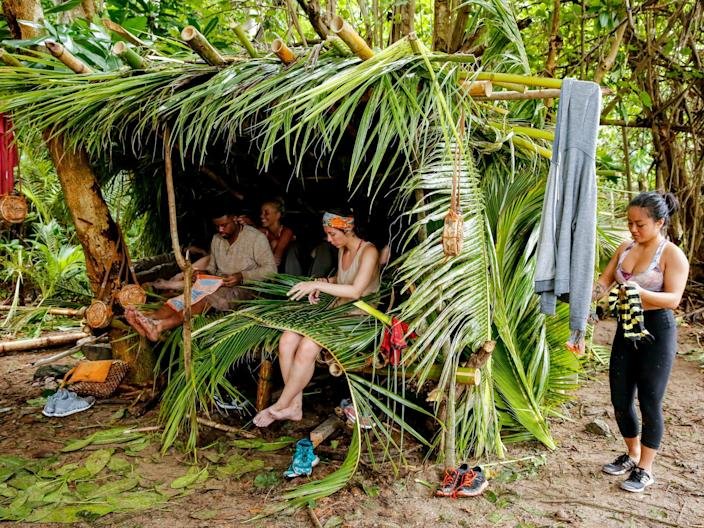 """Davie Rickenbacker and others at camping sitting in a palm leaf and bamboo hurt on """"Survivor"""""""