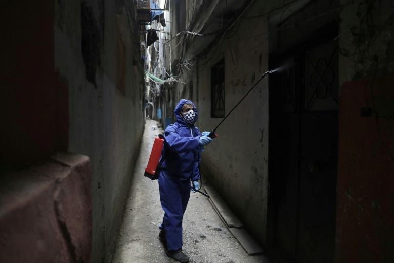 A volunteer sprays disinfectant in the narrow alleyways of the Shatila Palestinian refugee camp in the Lebanese capital Beirut (AFP Photo/ANWAR AMRO)