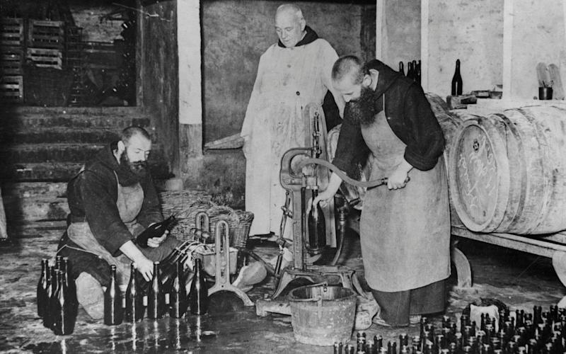 Monks work in the bottling room of the brewery at St. Sixtus Monastery in Westvleteren, Belgium. The brewery is one of the oldest in the world. - Corbis Historical