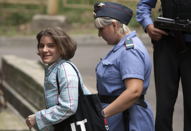 "Yekaterina Samutsevich, left, a member of feminist punk group Pussy Riot is escorted to a court room in Moscow, Russia, Tuesday, Aug. 7, 2012. Russia's President Vladimir Putin on Thursday criticized the feminist punk rockers facing trial for performing a ""punk prayer"" against him at Moscow's main cathedral, but said that a punishment for them shouldn't be too severe. (AP Photo/Alexander Zemlianichenko)"
