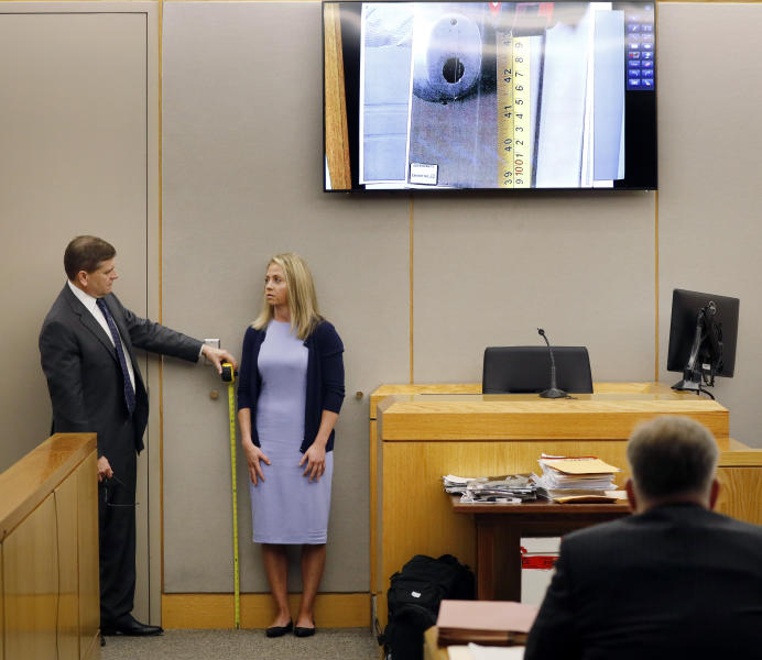 Defense attorney Toby Shook measures the height of a keyhole as fired Dallas police officer Amber Guyger stand against the courtroom wall as she testifies in her murder trial, Friday, Sept. 27, 2019, in Dallas. Guyger is accused of shooting and killing Botham Jean, an unarmed 26-year-old neighbor in his own apartment last year. She told police she thought his apartment was her own and that he was an intruder. (Tom Fox/The Dallas Morning News via AP, Pool)