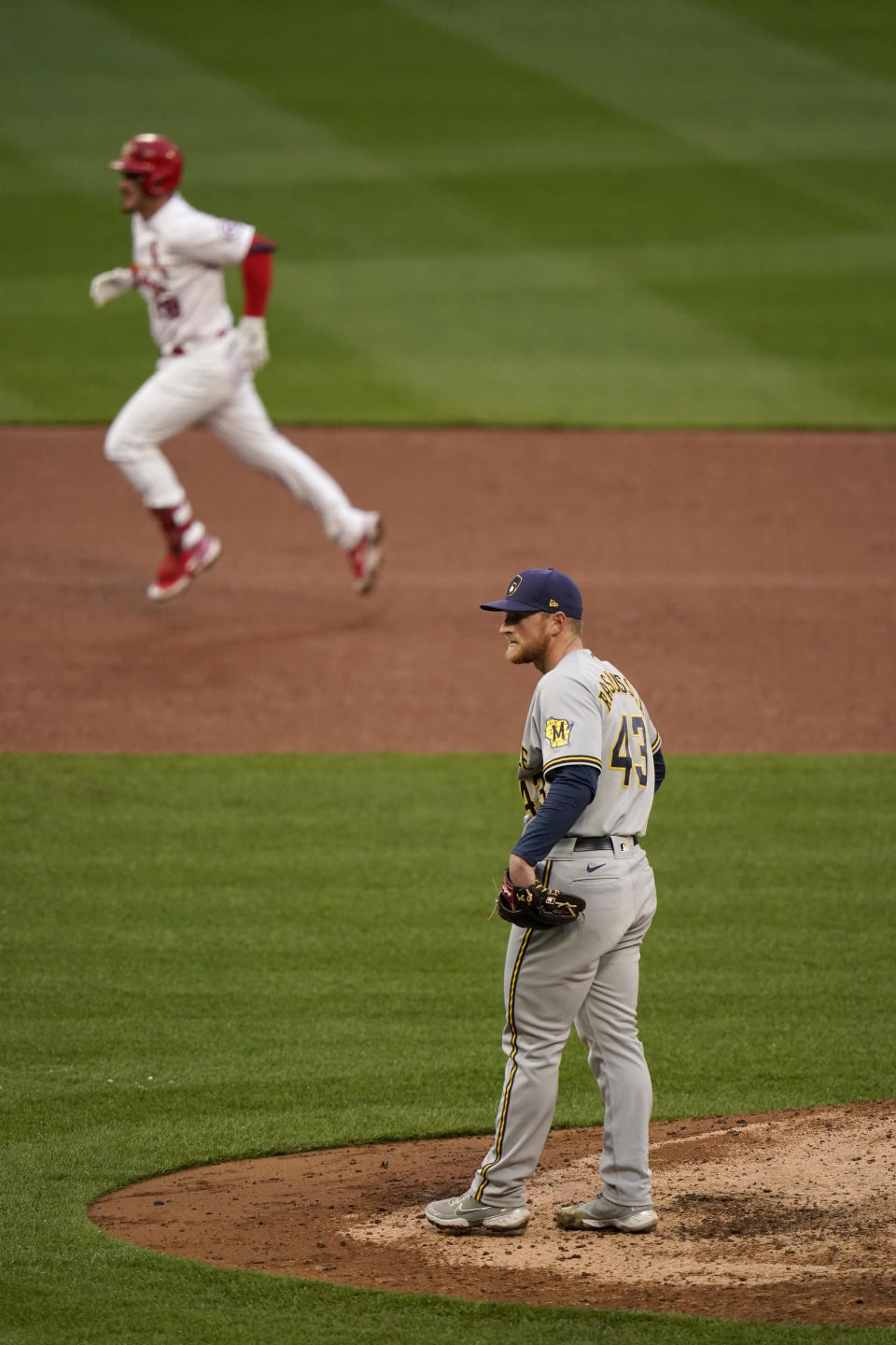 St. Louis Cardinals' Nolan Arenado, top, rounds the bases after hitting a two-run home run off Milwaukee Brewers relief pitcher Drew Rasmussen (43) during the eighth inning of a baseball game Thursday, April 8, 2021, in St. Louis. (AP Photo/Jeff Roberson)