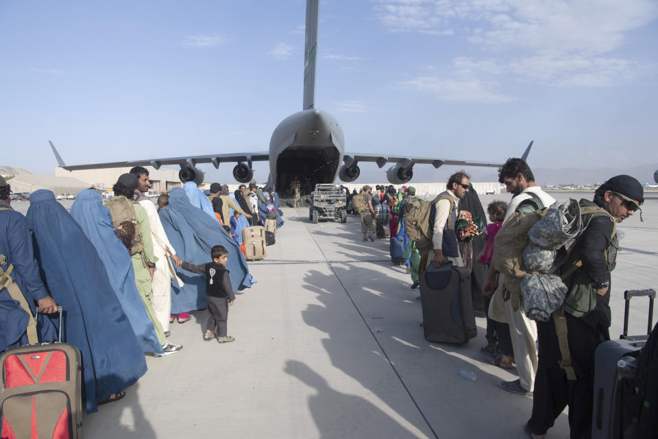 US Air Force loadmasters and pilots load people being evacuated from Afghanistan onto a US Air Force C-17 Globemaster III at Hamid Karzai International Airport in Kabul on Tuesday. Source: AAP