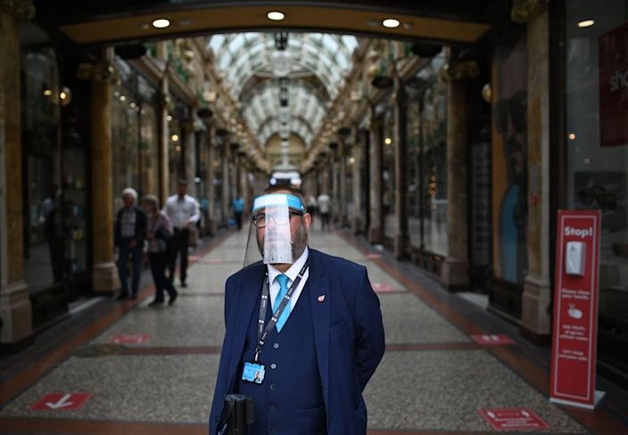 A member of staff stands at the entrance of the County Arcade wearing a PPE visor in the city centre of Leeds, on July 23, 2020, as England prepares to make the wearing of face coverings in shops mandatory as a new measure designed to combat the novel coronavirus COVID-19 pandemic. - The wearing of facemasks in shops in England will be compulsory from Friday, but full guidance is yet to be published. (Photo by Oli SCARFF / AFP) (Photo by OLI SCARFF/AFP via Getty Images)