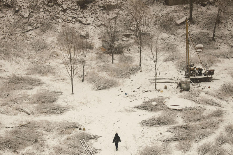 A man walks through the snow-covered surface of a work site in Beijing on Monday, Dec. 16, 2019. (AP Photo/Ng Han Guan)