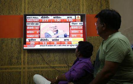 Men look at a television screen showing exit poll results after the last phase of the general election in Ahmedabad, May 19, 2019. REUTERS/Amit Dave