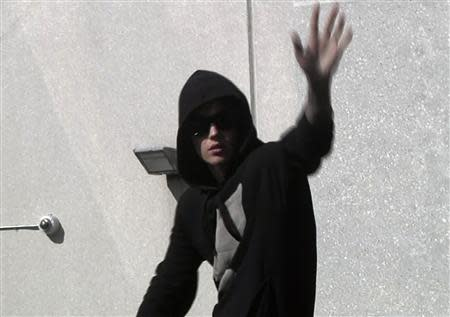 Pop singer Justin Bieber waves to fans as he leaves a jail after being released on bail in Miami, Florida in this still image taken from video January 23, 2014. REUTERS/Reuters TV