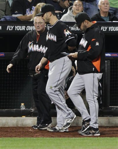 Miami Marlins center fielder Justin Ruggiano, center, is escorted off the field after being injured while fielding a ball hit by New York Mets' Scott Hairston during the fifth inning of a baseball game on Friday, Sept. 21, 2012, in New York. (AP Photo/Frank Franklin II)