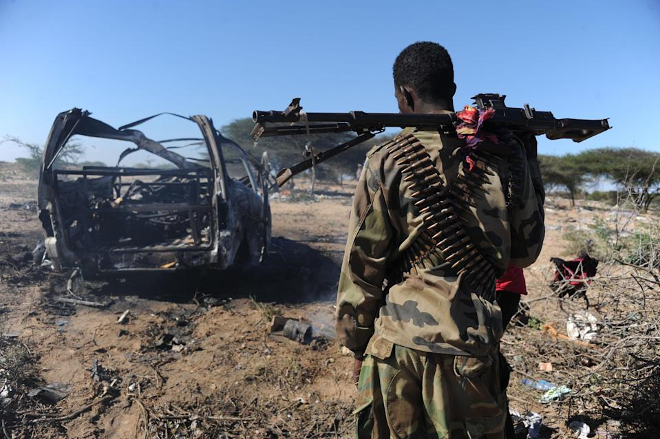 A Somali soldier checks a suicide bombing site in Mogadishu on September 8, 2014, (AFP Photo/Mohamed Abdiwahab)