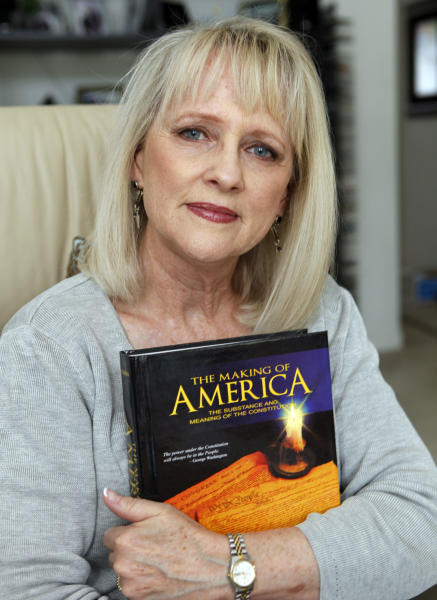 """In this Monday, May 7, 2012 photo, lawyer Linda J. Hoover holds a book on the U.S. Constitution at her home in Centennial, Colo. Hoover has cited a March USA Today/Gallup poll of swing states, including Colorado, that showed women favoring Obama over Romney by 18 percentage points. """"It's absolutely frightening how quickly, once they launched that (war) narrative ... the polling data changed. I'm hoping it was a short-term bounce, but let's not assume that,"""" said Hoover, 60, who has been working voter registration booths to do her part in enticing more women voters. (AP Photo/Ed Andrieski)"""