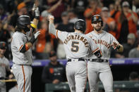 San Francisco Giants' Mike Yastrzemski, center, is congratulated by Brandon Crawford, left, and Evan Longoria after Yastrzemski hit a three-run home run off Colorado Rockies relief pitcher Ashton Goudeau in the seventh inning of a baseball game Friday, Sept. 24, 2021, in Denver. (AP Photo/David Zalubowski)
