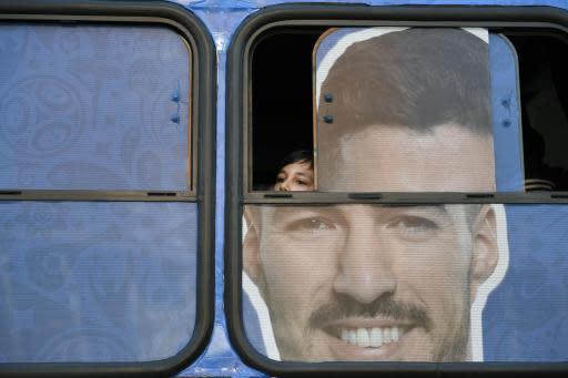 A boy peers out the window of a bus with a large image of Uruguay's national soccer player Luis Suarez image plastered on it, during a television broadcast of the Russia 2018 World Cup match between Saudi Arabia and Uruguay in Montevideo, Uruguay, Wednesday, June 20, 2018. (AP Photo/Matilde Campodonico)