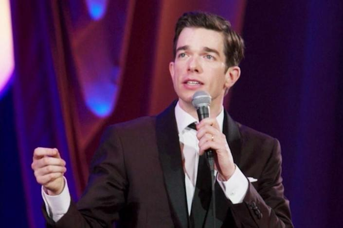 John Mulaney performing a stand-up in a dark brown suit