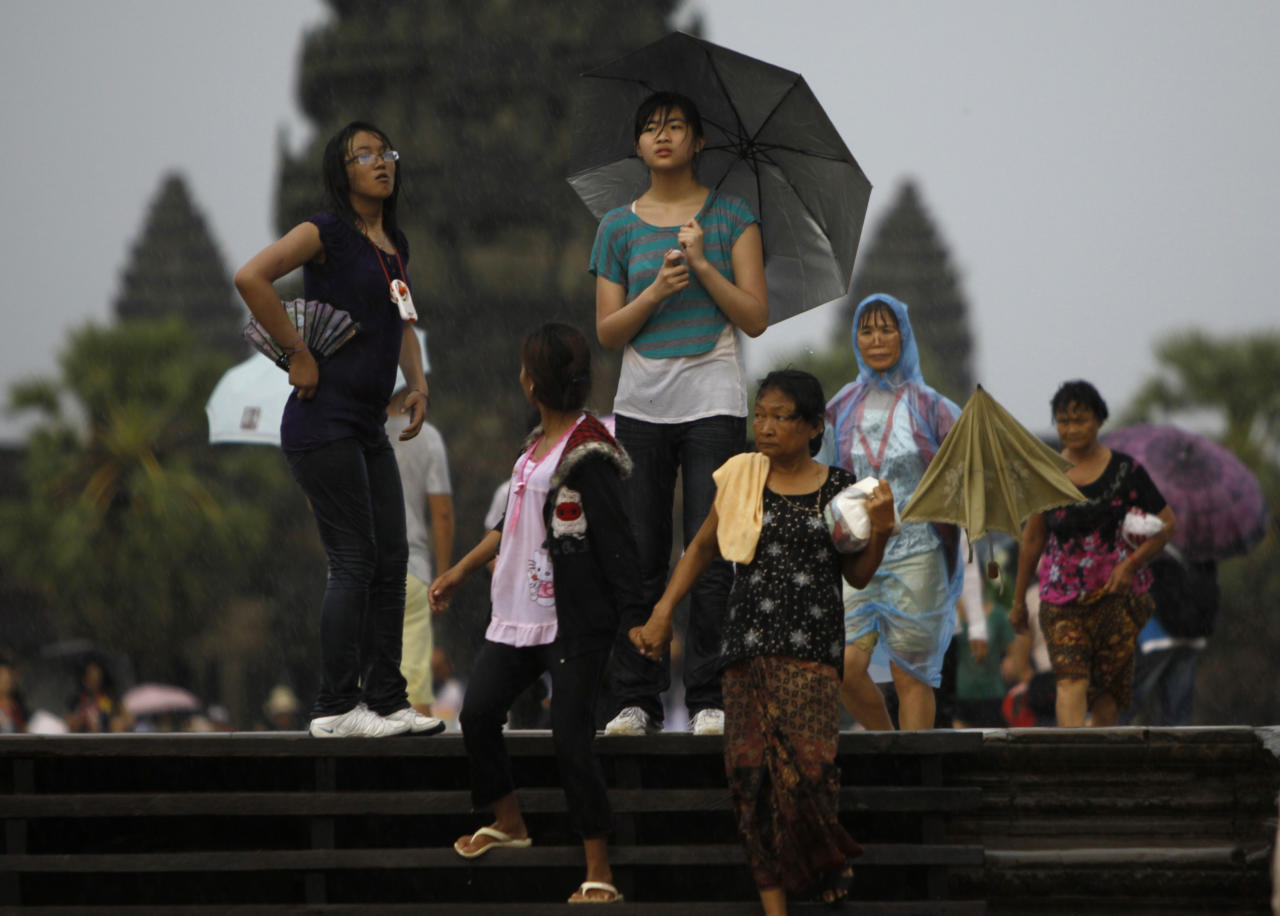 Tourists walk in the rain through an entrance of the famed Angkor Wat in eastern Siem Reap province, some 230 kilometers (143 miles) northwest of Phnom Penh, Cambodia, Saturday, July 2, 2011. Siem Reap is Cambodia's main tourist destination where famed Angkor temples are located. (AP Photo/Heng Sinith)