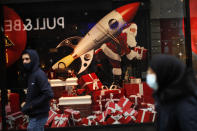 People, wearing face masks to prevent the spread of the coronavirus, walk past a shopping mall display windows with Christmas decoration in a commercial street in downtown Brussels, Tuesday, Dec. 1, 2020. Non-essential shops in Belgium are reopening on Tuesday in the wake of encouraging figures about declining infection rates and hospital admissions because of the coronavirus. (AP Photo/Francisco Seco)