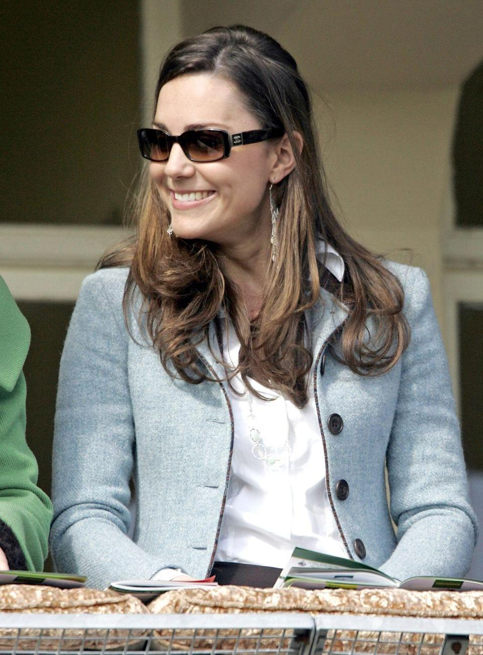 <p>Smiling at the Cheltenham Festival Race Meeting in sunglasses and a pale blue blazer.</p>