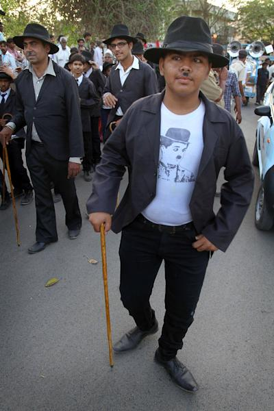 Members and supporters of the Charlie Circle, a Charlie Chaplin fan-club, participate in an annual parade to celebrate the birthday of Charlie Chaplin in Adipur, Gujarat state, India, Tuesday, April 16, 2013. Canes in hand and bowler hats firmly in place, dozens of Charlie Chaplin impersonators tramped through the streets of this small port town in western India on Tuesday to celebrate the birthday of the legendary comic actor and filmmaker. (AP Photo/Ajit Solanki)