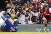Fans reacts as Boston Red Sox's Christian Vazquez, right, picks off Toronto Blue Jays' Reese McGuire at home plate during the second inning of a baseball game, Saturday, June 12, 2021, in Boston. (AP Photo/Michael Dwyer)