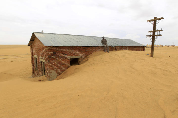 <p>A worker rests on the roof of a building surrounded by sand as a result of desert encroachment at Ogrein Railway Station, Sudan, Aug. 1, 2013. (Mohamed Nureldin Abdallah/Reuters) </p>