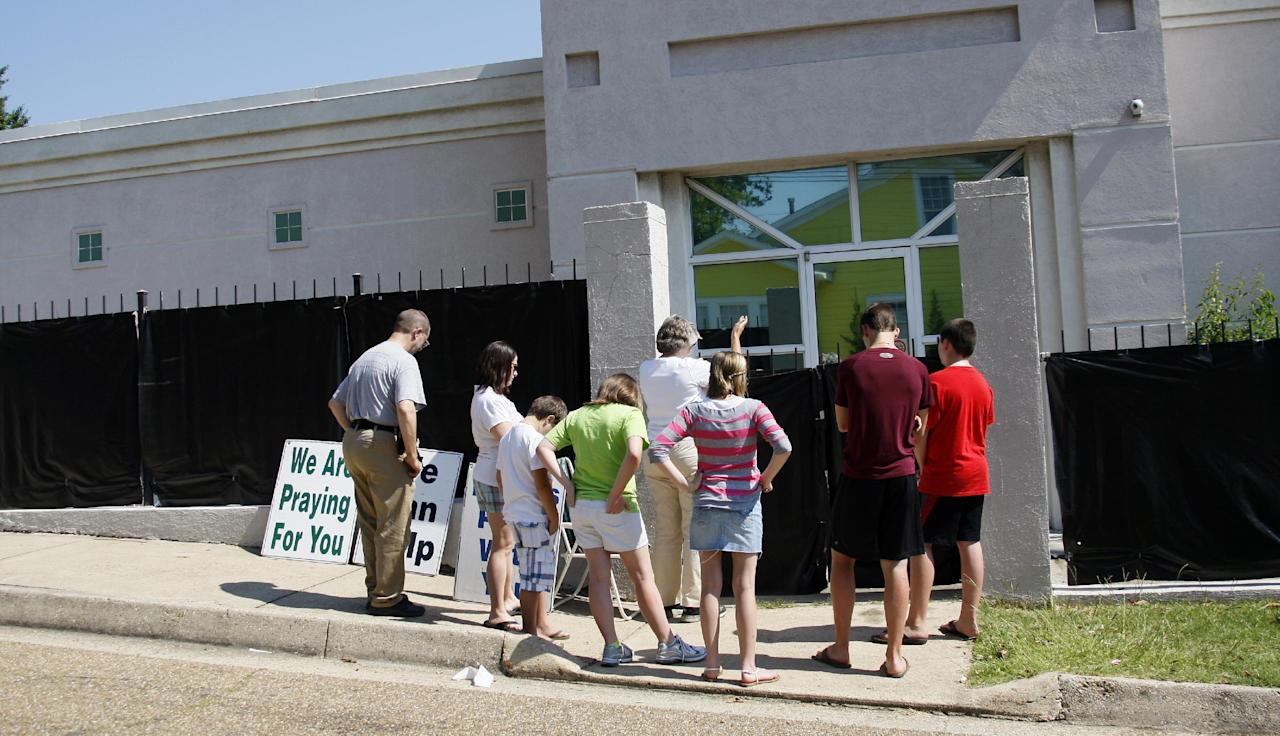 """In this June 27, 2012 photograph, anti-abortion advocates stand outside Mississippi's only abortion clinic, singing and praying for their patients, and """"counseling"""" them to reject abortion. Mississippi could soon become the only state without an abortion clinic because of a new law taking effect July 1. Critics say the law would force women to drive hours across the state line to obtain a constitutionally protected procedure, or could even force some to carry unwanted pregnancies to term.The clinic's owner, Jackson Women's Health Organization, sued Wednesday, in a federal lawsuit to stop a law that it says will effectively ban abortion in the state and endanger women's health by limiting access to the procedure. (AP Photo/Rogelio V. Solis)"""