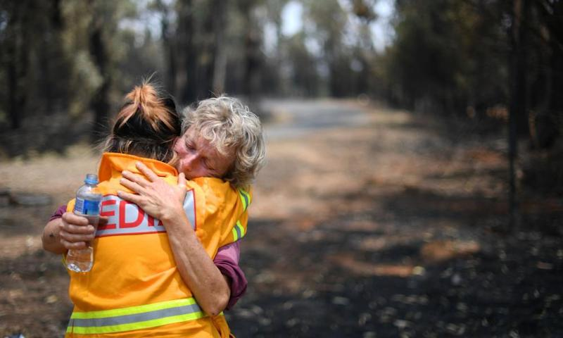 Orchardist Stephenie Bailey reacts as she describes the impact bushfires have had on her farm in Batlow, NSW.