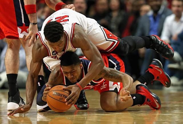CHICAGO, IL - APRIL 22: Jimmy Butler #21 of the Chicago Bulls lands on top of Bradley Beal #3 of the Washington Wizards as they battle for a loose ball in Game Two of the Eastern Conference Quarterfinals during the 2014 NBA Playoffs at the United Center on April 22, 2014 in Chicago, Illinois. (Photo by Jonathan Daniel/Getty Images)