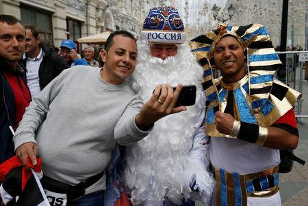 Supporters of the Egyptian national soccer team take a selfie with a street performer dressed as Father Frost, the Russian equivalent of Santa Claus, on the eve of the 2018 FIFA World Cup in central Moscow, Russia June 14, 2018. REUTERS/Gleb Garanich