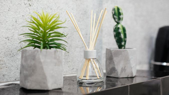 Air fresher and house plants in pots on the stone black tale closeup.