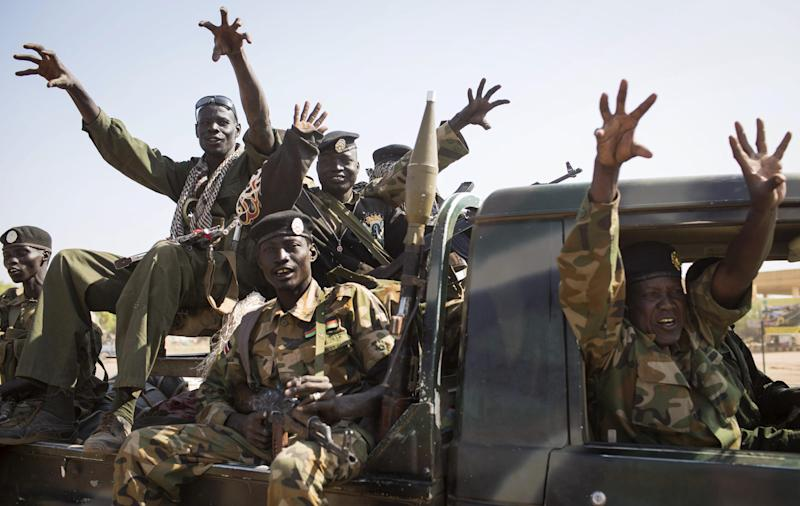 """FILE - In this Sunday, Jan 12, 2014 file photo, South Sudanese government forces from the """"Lion division"""" cheer their recent victory, after government forces on Friday retook from rebel forces the provincial capital of Bentiu, in Unity State, South Sudan. South Sudan's government and rebels fighting against it have signed Thursday, Jan. 23, 2014 a cessation of hostilities agreement in Addis Ababa that should at the least put a pause to five weeks of warfare that has claimed thousands of lives and uprooted a half million people since fighting began Dec. 15 between the government and supporters of former Vice President Riek Machar. (AP Photo/Mackenzie Knowles-Coursin, File)"""