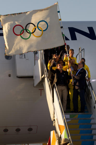 Rio de Janeiro's Mayor Eduardo Paes, bottom left, and Carlos Arthur Nuzman, President of the Brazilian Olympic Committee, hold up the Olympic flag upon its arrival in Rio de Janeiro, Brazil, Monday, Aug. 13, 2012. The flag's arrival marks the official start of Rio's Olympic preparations, with the city to undertake nearly 200 projects to construct sports venues and other infrastructure during the next four years. (AP Photo/Silvia Izquierdo)
