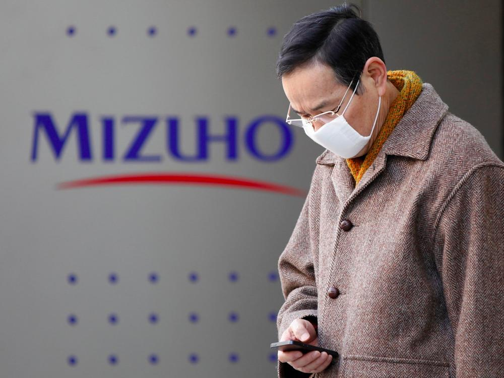 A man uses a smartphone in front of a branch of Mizuho bank, belonging to Mizuho Financial Group, in Tokyo January 29, 2013. Mizuho Financial Group Inc, Japan's second-largest lender by assets, reported a 45 percent increase in net profit for the nine months ended December, helped by a year-end rally in Japanese equities. Picture taken January 29, 2013.