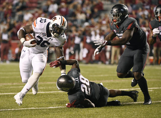 "Auburn running back <a class=""link rapid-noclick-resp"" href=""/ncaaf/players/242648/"" data-ylk=""slk:Kamryn Pettway"">Kamryn Pettway</a> (36) slips past Arkansas defenders <a class=""link rapid-noclick-resp"" href=""/ncaaf/players/244193/"" data-ylk=""slk:Josh Liddell"">Josh Liddell</a> (28) and <a class=""link rapid-noclick-resp"" href=""/ncaaf/players/266534/"" data-ylk=""slk:De'Jon Harris"">De'Jon Harris</a> (8) as he runs for a touchdown during the second half of an NCAA college football game in Fayetteville, Ark., Saturday, Oct. 21, 2017. (AP Photo/Michael Woods)"