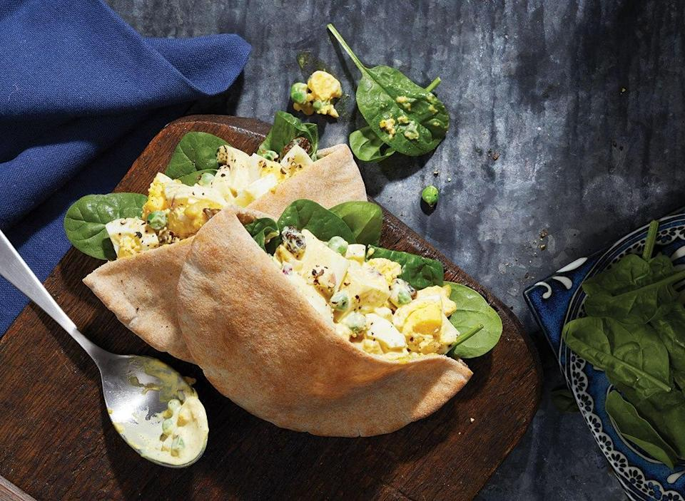 curried egg salad in pita pocket with spoon and bowl of spinach on wooden serving board with blue linen napkin