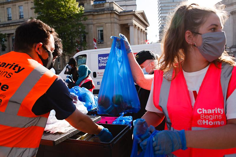 Volunteers from the Charity Begins At Home non-profit group hand out food parcels at a 'mobile food bank' in Trafalgar Square in London, England, on May 15, 2020. (Photo by David Cliff/NurPhoto via Getty Images)