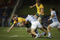 Australia's Matt Philip, left, is tackled by Argentina's Nahuel Tetaz Chaparro, center, during their Tri-Nations rugby union match in Newcastle, Australia, Saturday, Nov. 21, 2020. (AP Photo/Rick Rycroft)