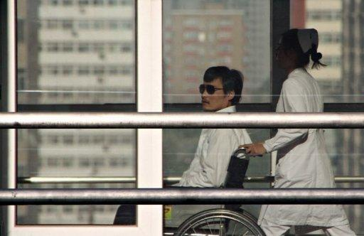 Chinese activist activist Chen Guangcheng (L) is seen in a wheelchair pushed by a nurse at the Chaoyang hospital