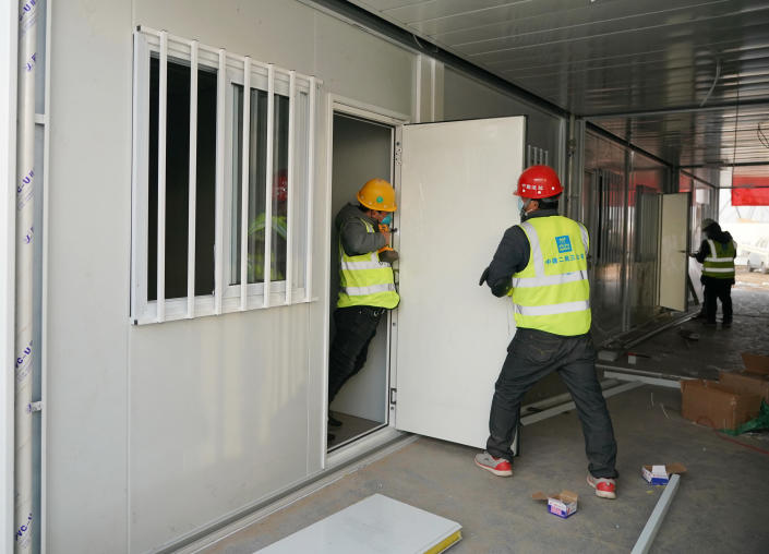 In this photo released by China's Xinhua News Agency, workers install doors at a large centralized quarantine facility capable of holding several thousand people in Shijiazhuang in northern China's Hebei Province, Saturday, Jan. 16, 2021. China on Saturday finished building a 1,500-room hospital for COVID-19 patients in Nangong, south of Beijing in Hebei Province, to fight a surge in infections the government said are harder to contain and that it blamed on infected people or goods from abroad. (Yang Shiyao/Xinhua via AP)