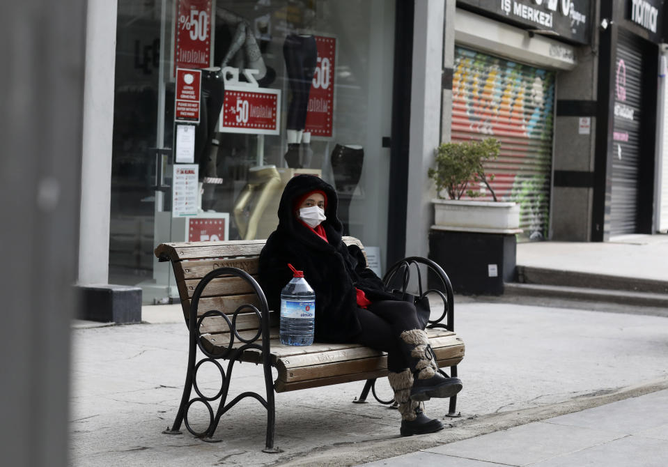 A woman wearing a mask to help protect against the spread of coronavirus, rests in a deserted street after shopping for food during a two-day weekend curfew, in Ankara, Turkey, Sunday, Jan. 24, 2021. Turkey has passed the milestone 25,000 COVID-19 deaths on Sunday. (AP Photo/Burhan Ozbilici)