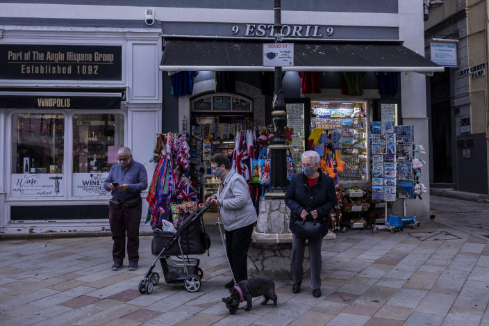 """Two elderly woman walk past a souvenir shop in Gibraltar, Thursday, March 4, 2021. Gibraltar, a densely populated narrow peninsula at the mouth of the Mediterranean Sea, is emerging from a two-month lockdown with the help of a successful vaccination rollout. The British overseas territory is currently on track to complete by the end of March the vaccination of both its residents over age 16 and its vast imported workforce. But the recent easing of restrictions, in what authorities have christened """"Operation Freedom,"""" leaves Gibraltar with the challenge of reopening to a globalized world with unequal access to coronavirus jabs. (AP Photo/Bernat Armangue)"""