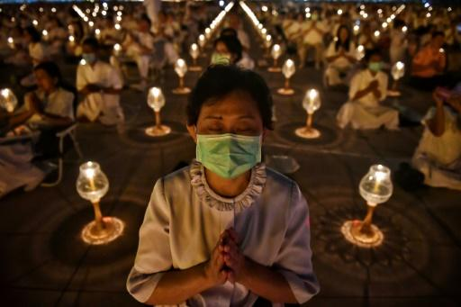 Buddhist worshippers wearing protective masks attend prayers at Wat Dhammakaya Buddhist temple in Bangkok -- Thailand has announced 14 confirmed coronavirus infections