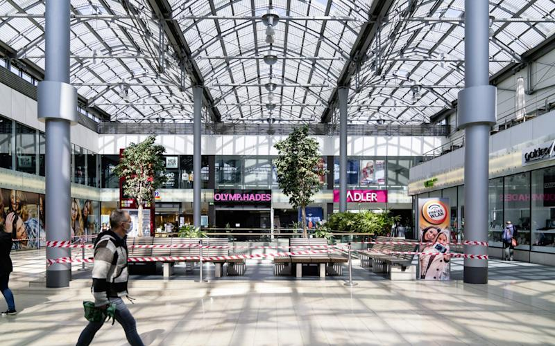 A pedestrian wearing a protective face mask passes a cordoned off seating area inside the Rathaus Galerie shopping mall in Essen, Germany, on Wednesday, April 15, 2020. Germany is poised to agree on an extension of most restrictions on public life into next month, underlining how European governments are struggling to balance reactivating their economies against fears of a resurgence of the coronavirus. Photographer: Wolfram Schroll/Bloomberg - Wolfram Schroll/ Bloomberg