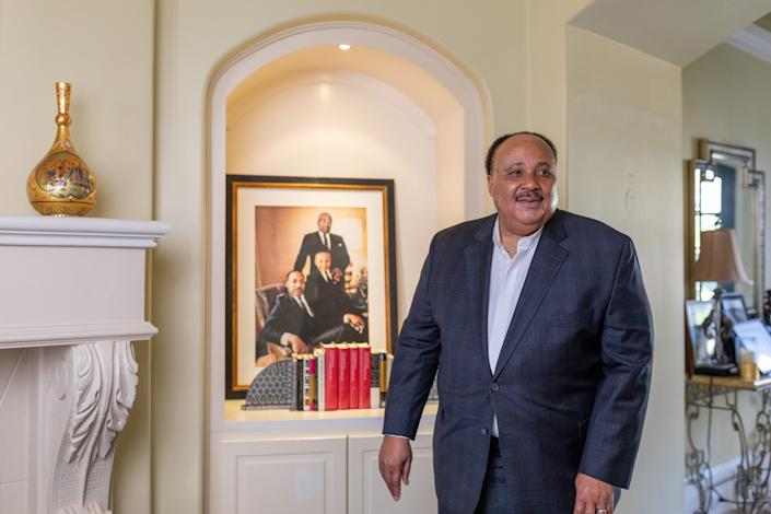 Martin Luther King III stands in front of a portrait of him and his father, Martin Luther King Jr.
