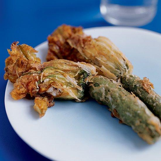 """<p>In Greece, zucchini flowers are often added to vegetable <a href=""""https://www.foodandwine.com/slideshows/light-stews"""" target=""""_blank"""">stews</a> or to grated zucchini and cheese for savory pies.</p> <p> <a href=""""http://www.foodandwine.com/recipes/fried-zucchini-blossoms"""">Go to Recipe</a></p>"""