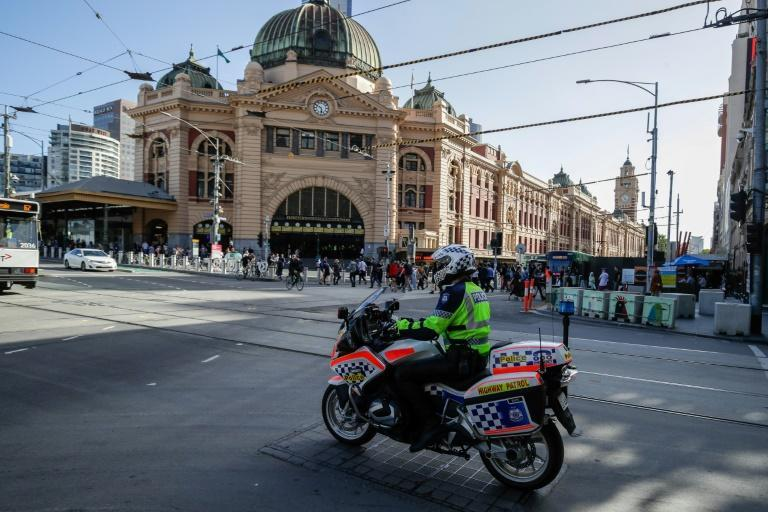 A policeman patrols Melbourne after authorities ordered a five-day state-wide coronavirus lockdown starting at midnight local time