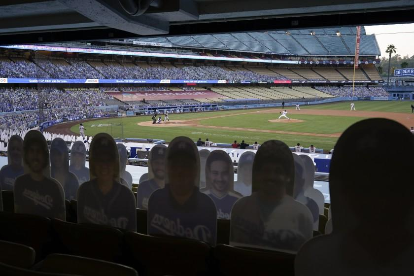 Cutouts of fans sit in the stands as Los Angeles Dodgers starting pitcher Clayton Kershaw, right, throws to Arizona Diamondbacks' Christian Walker during the first inning of a baseball game Thursday, Sept. 3, 2020, in Los Angeles. (AP Photo/Marcio Jose Sanchez)